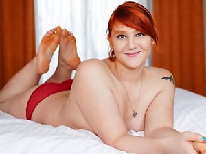 Busty redhead shemale posing solo in the bed